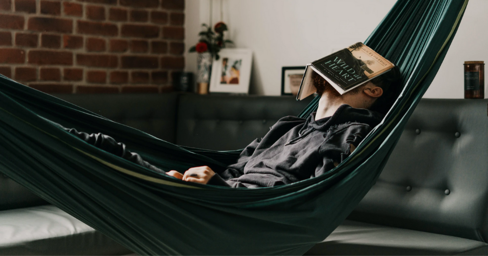 man sleeps with book on his face while lying in an indoor hammock in a modern home