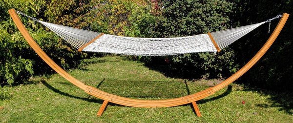 Durable and eco-friendly solid multi-ply bamboo board hammock stand with rope hammock pictured in backyard.