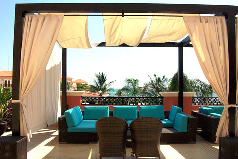Turquoise outdoor couch under brown pergola with cream curtains, palm trees in the background.