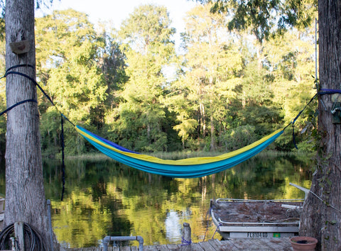 Blue and yellow hammock hanging between two trees in front of a lake