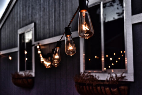 Outdoor hanging string lights with barn in background