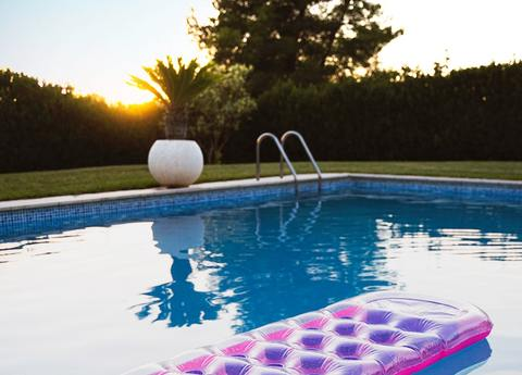 Swimming pool with pink floatie at sunset