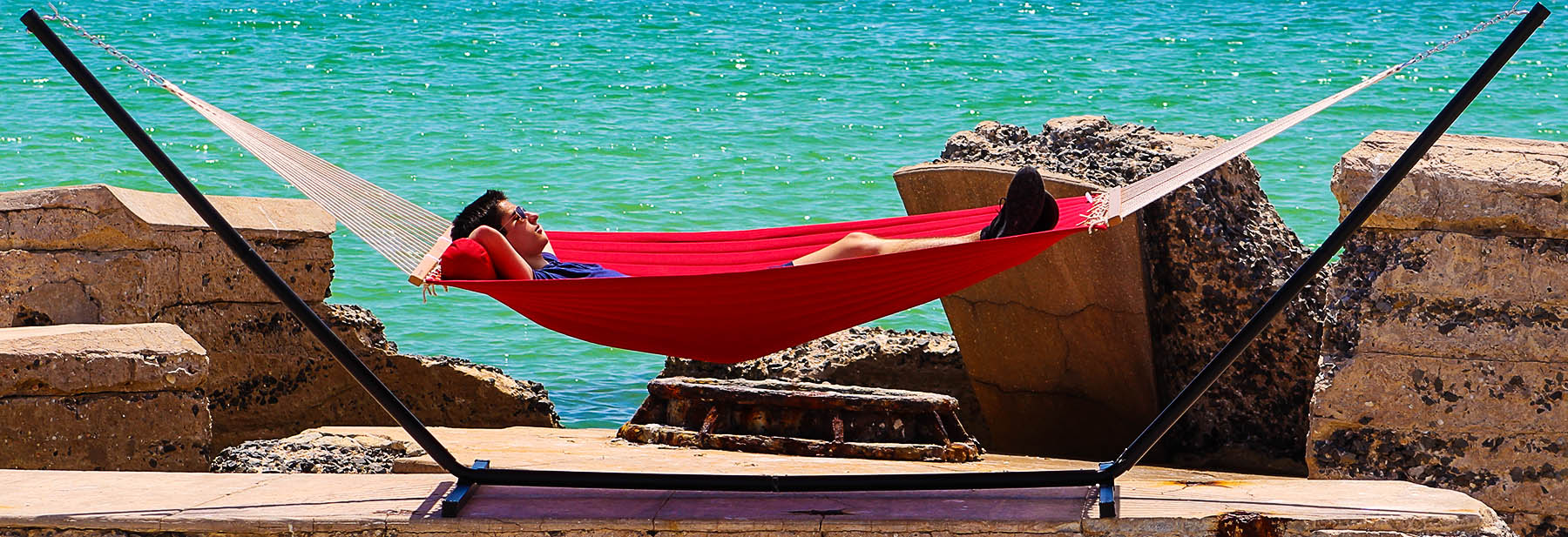 young man resting in a red hammock and stand by the ocean
