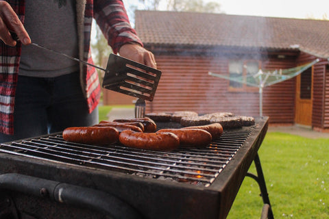 Person barbecuing sausages