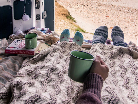 Two people in the back of a van with a blanket drinking coffee