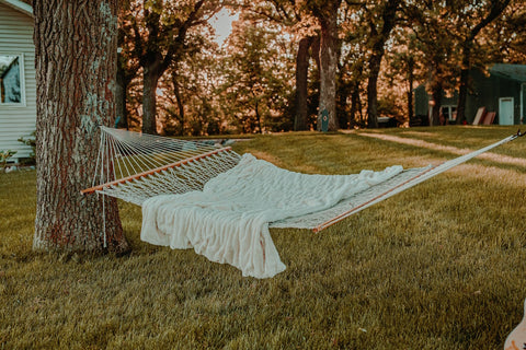 White rope hammock with a white blanket on top