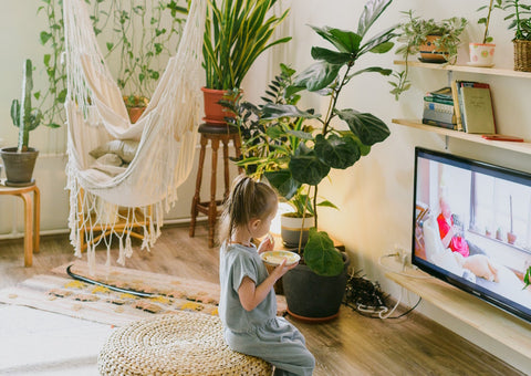 Little girl watching TV next to a white hammock