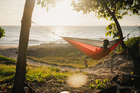 Man sitting in red and black hammock in front of the beach at sunset