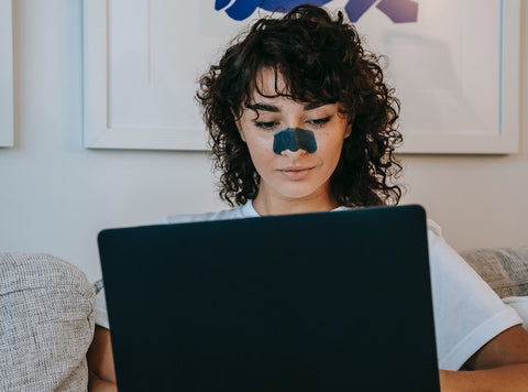 Woman with nose strip in front of her laptop