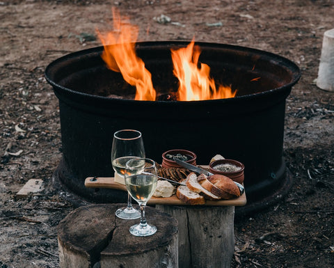 Firepit with plate of food and wine glasses