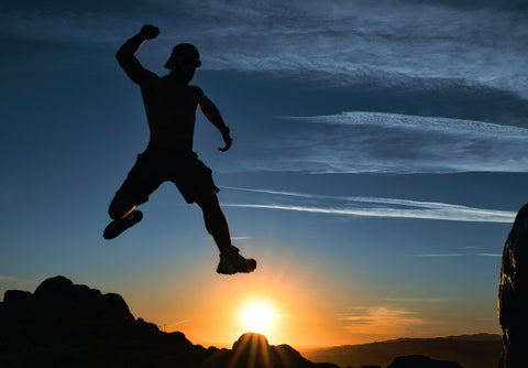 Man jumping in the air pumping his fist at sunset