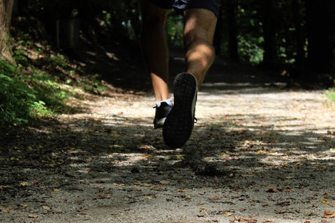 Close up shot of man's feet while running on a trail