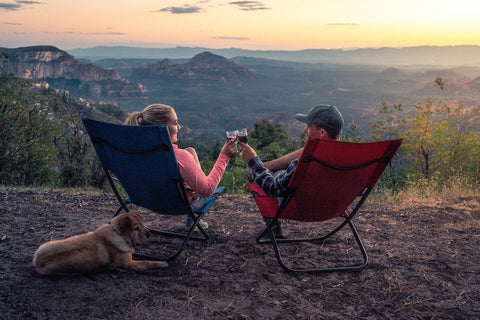 Man and woman sitting in camping chairs overlooking a cliff toasting glasses