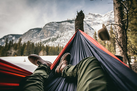 Man wearing work boots in a camping hammock overlooking mountains