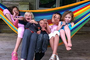 children enjoying themselves in a colourful mayan hammock