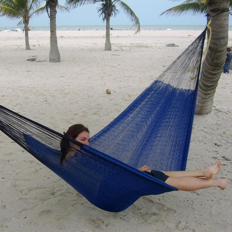 Woman sitting in a blue hammock on the beach with palm trees