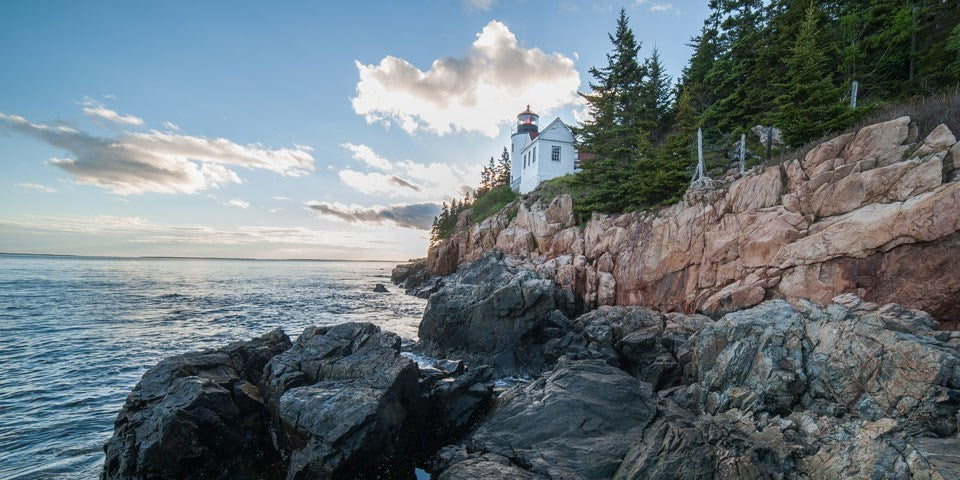 Shoreline of Acadia National Park with a lighthouse in the background