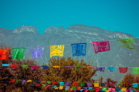 Colourful handkerchieves hanging on a clothesline outside in front of mountains
