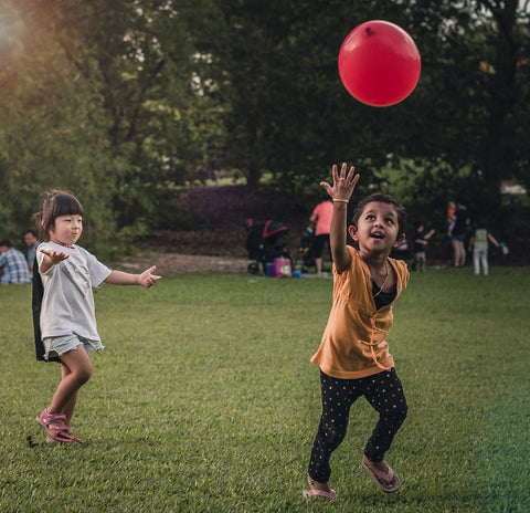 Two young children play chasing a red balloon