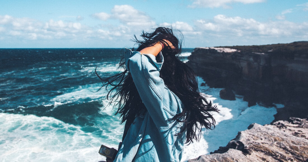 black-haired woman stands on a cliff overlooking the ocean