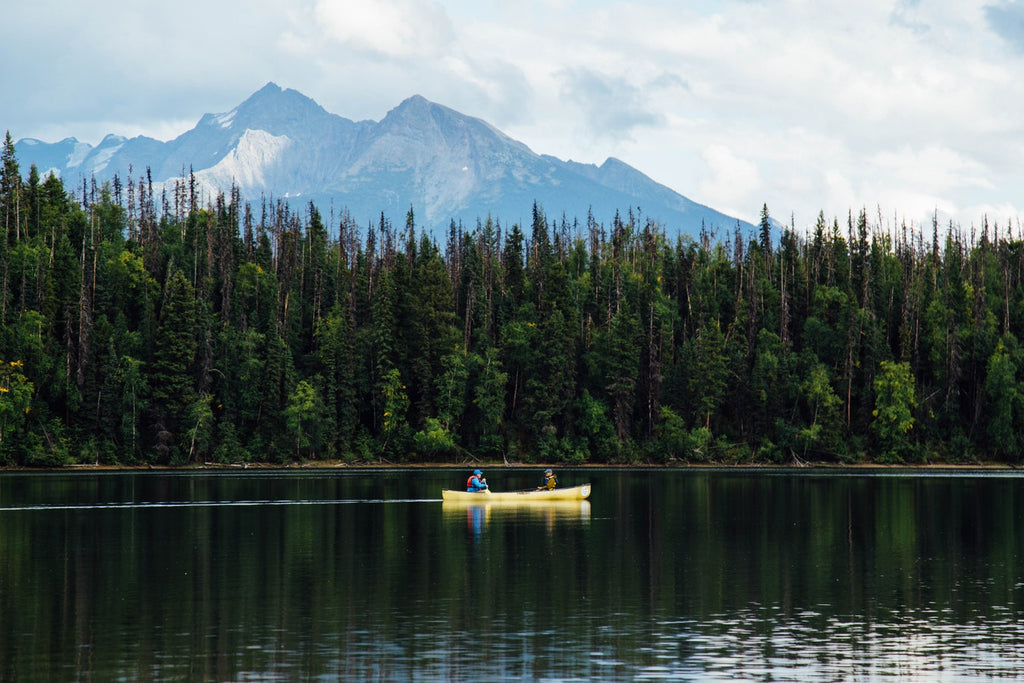 A yellow canoe paddles across a beautiful clear lake sitting at the foot of British Columbian mountains.