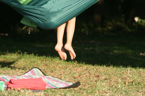 Child sitting in hammock safely outdoors