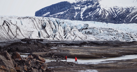 Two people in red exploring a glacier