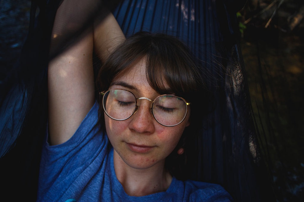 Girl wearing glasses relaxes and sleeps in hammock