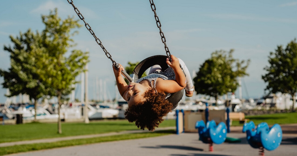 young child swings upside down at the park