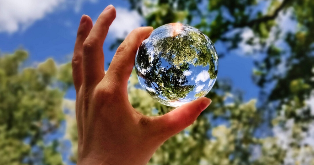 hand holds up glass ball in front of trees
