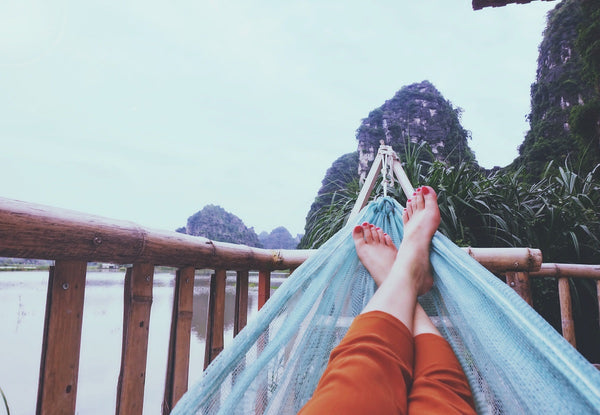 A pair of crossed legs with bare feet and painted toenails sit in a blue hammock in a stand on a deck overlooking mountains and the sea.