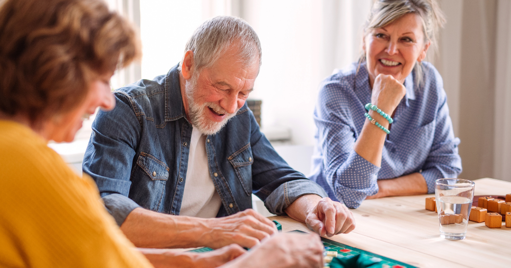 older family plays board games at the kitchen table