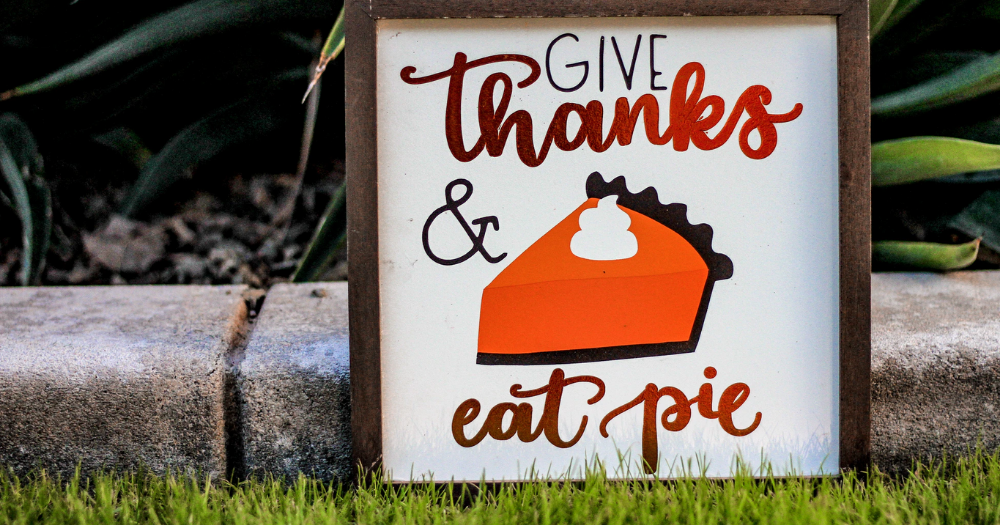 """outdoor sign with pumpking pie on it that says """"give thanks, eat pie"""""""
