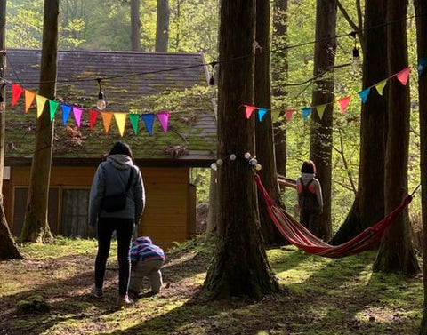 woman and her two young children in the woods with streamers and a hammock and cabin in the background
