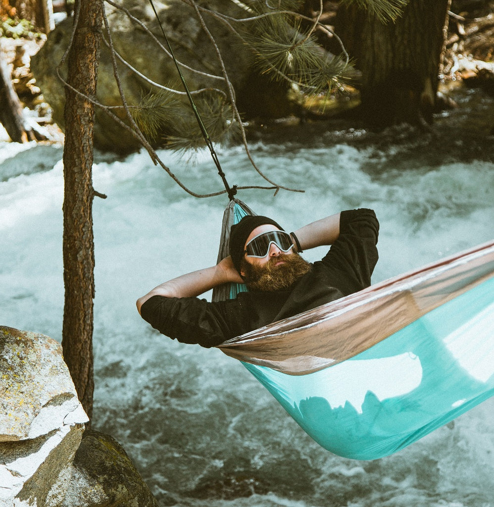 Bearded camper hangs in a hammock tied to a tree over a running water stream.