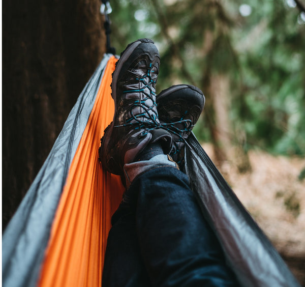 Camper lies on a nylon hammock tied to a tree.