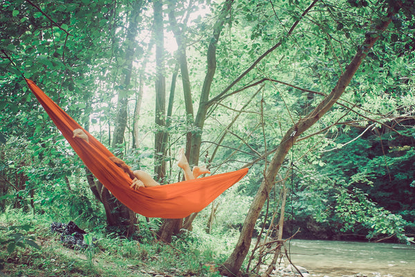 Woman hangs in an orange hammock between trees in the forest.