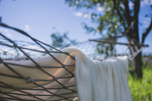 Close-up of rope hammock and blanket outside on a sunny day.