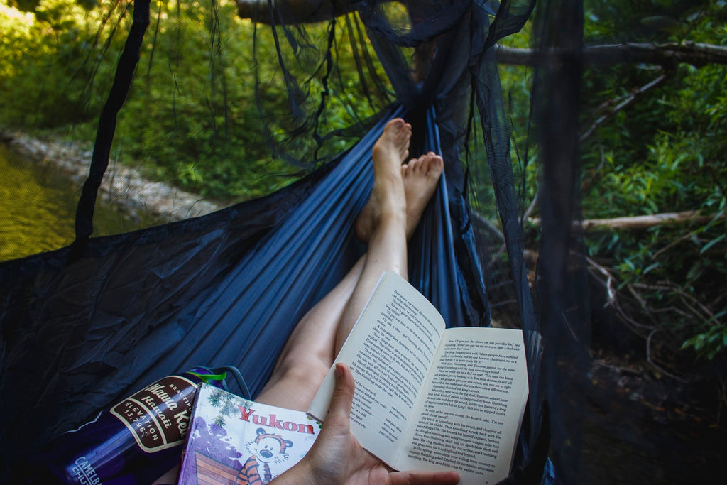 A person reading a book lies in a hammock with built-in mosquito netting.