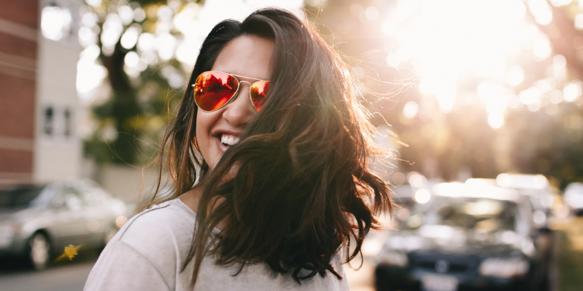 woman wearing sunglasses smiles outside