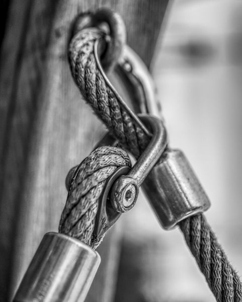 Close-up image of rope and clips secured into a wooden beam.