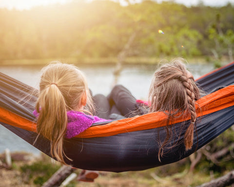 Two young girls sitting in a hammock facing a lake