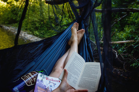 Person reading a book in a blue hammock in the forrest.