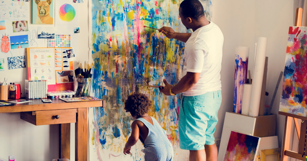 father and child paint mural on wall as indoor decor project