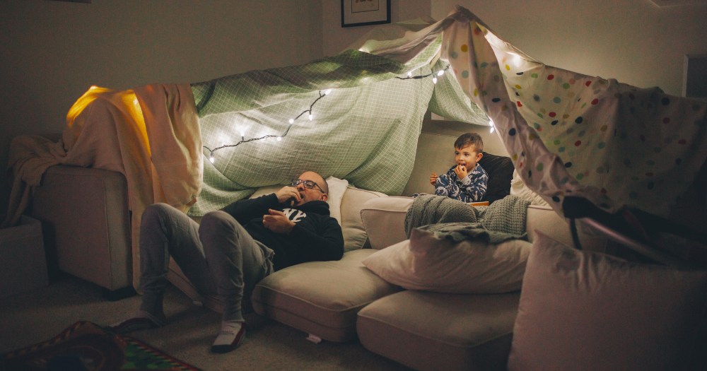 father and son build a fort in the living room