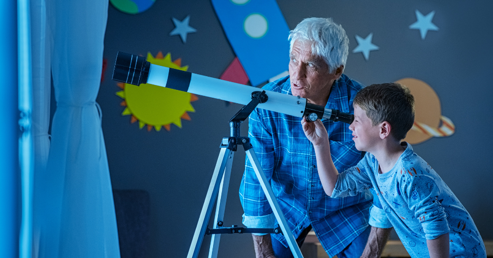 grandfather and grandson learn about the stars using indoor telescope