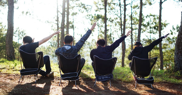 four millennials dabbing on a camping site
