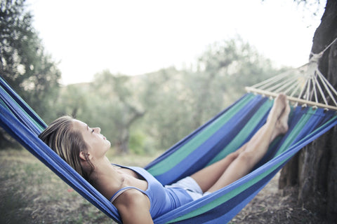 Woman sleeping outdoors in a blue and green striped hammock