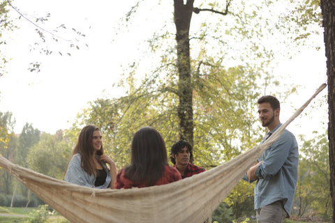 A group of men and women sitting outdoors in a large hammock