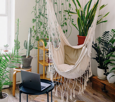 A cream, crochet hammock hanging in a living room in front of an open laptop